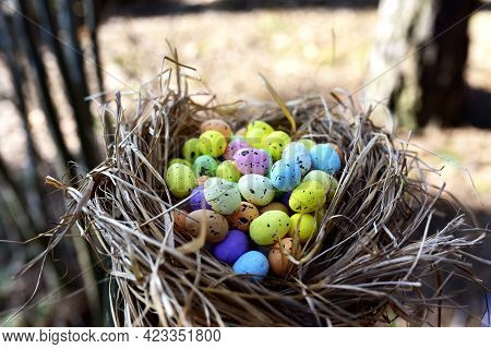 Multi-colored Easter Eggs In A Bird\'s Nest. Straw And Twig Bird Nest With Egg. Easter Is A Christia