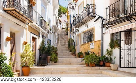 Narrow Street With Steps, White Houses And Potted Plants In Ancient Neighborhood El Barrio Or Casco