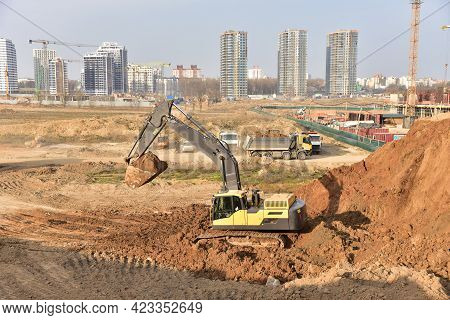 Excavator During Earthmoving Work At Construction Site. Backhoe Digging Ground For Foundation Pit. O