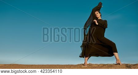 Fashion shot. Beautiful brunette woman in a long black dress posing in the desert with a scarf fluttering in the wind. Sky background. Copy space.