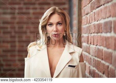 Portrait of an attractive middle-aged woman with enlarged full lips and evening makeup standing in white jacket in a room with brick walls. Cosmetology, plastic surgery, rejuvenation.