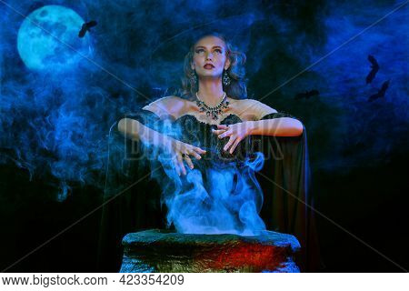 Halloween. A mysterious and gorgeous witch conjures over a cauldron at night on a full moon.