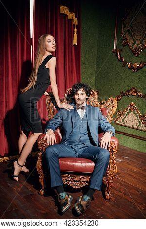 Beautiful elegant couple in fashionable evening clothes posing in a luxury vintage apartment. Glamorous lifestyle. Fashion shot.