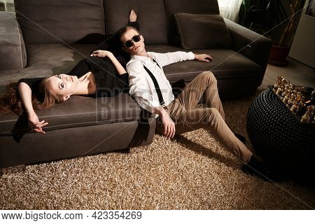 Glamorous lifestyle. Fashionable couple of young people in elegant clothes and sunglasses posing in a luxury apartment. Fashion shot.
