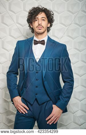 Portrait of a handsome brunet man in elegant blue suit and a bow-tie posing at studio. Men's fashion.
