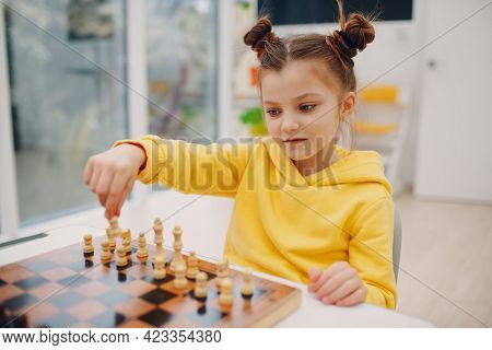 Little Girl Hold Chess Figure In Hand Above Chess Board. Child Playing Chess At Kindergarten Or Elem