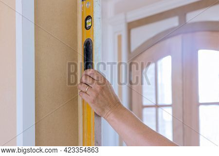 Wood Columns Using Level In Check Appropriate Under Construction In Worker Using Leveling Instrument