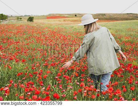 A Girl In A Summer Hat Walks Through A Blooming Poppy Field In Summer. Nature Pastime Theme.