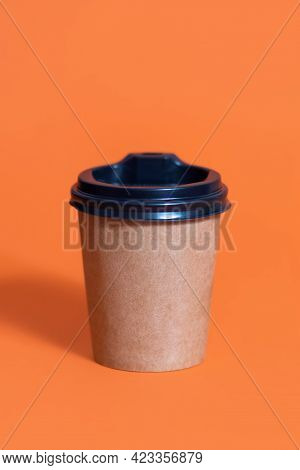 Disposable Coffee Cup For Cafe On Orange Background. Development Of The Corporate Identity Of The Re