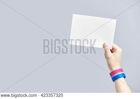 Young Hand With A Bisexual Flag Bracelet Holding A Blank Piece Of Paper. Concepts Of Equality, Non-d