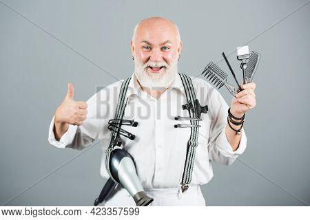 Old Happy Hairdresser, Funny Mature Barber. Portrait Of Senior Barber Holding Barber Equipments, Iso