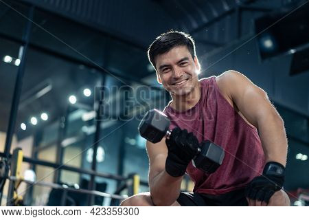 Portrait Of Young Caucasian Attractive Sportsman Workout Exercising To Maintain Muscle And Biceps In