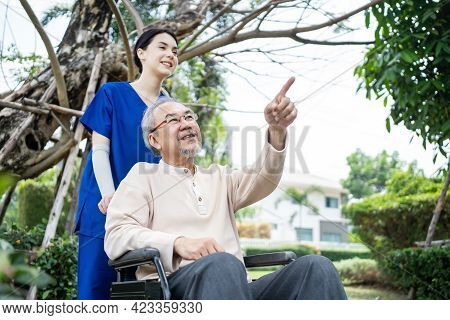Asian Happy Senior Retired Grandfather Have Fun Outdoor, Pointing At Green Park With Young Woman Nur