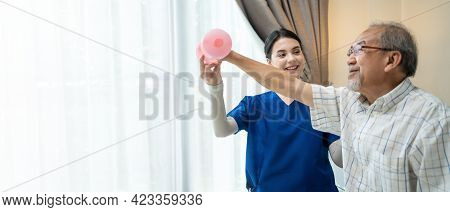 Asian Young Woman Nurse At Home Nursing Care Support Disabled Senior Elderly Man. Caregiver Therapis