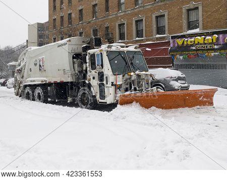 Bronx, New York/usa - February 1, 2021: Sanitation Truck Shovels Snow During Storm On Local Street.