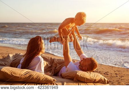 Dad Tosses His Son Up. Lie On A Bed By The Sea At Sunset. Family Vacation On The Sandy Beach. Young