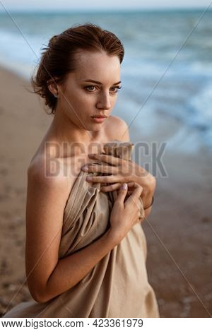 Lonely Looking Into The Distance On The Beach At Sunset. Summer Evening By The Water. Beautiful Youn