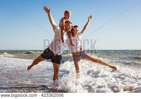 Happy Family Having Fun On Summer Vacation. Happy Son Sits On His Dads Neck. Cheerful Young Family O