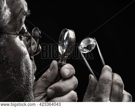 Large gemstone in jeweler's hand close up. Gem identifying and evaluating process.