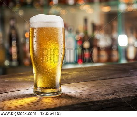 Cooled glass of pale beer with condensation drops on glass surface on the wooden table. Blurred bar at the background.