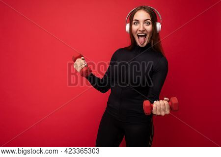 Attractive Positive Smiling Young Brunette Woman Wearing Black Sport Clothes Isolated On Red Backgro