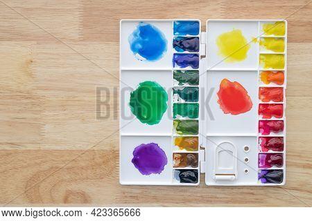 Colorful Watercolor Paints Set In Watercolour Palette On Wood. Multicolored Aquarelle Paints In Pain