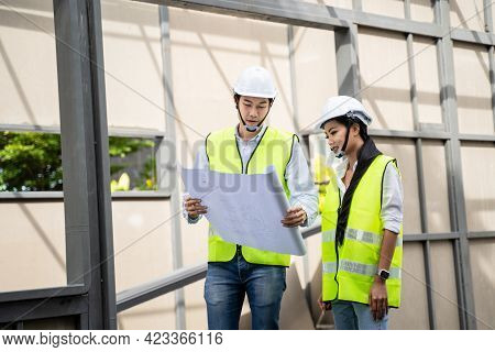 Asian Colleagues Worker Specialists Team Wearing Protective Safety Helmet Look At Blueprint On Const