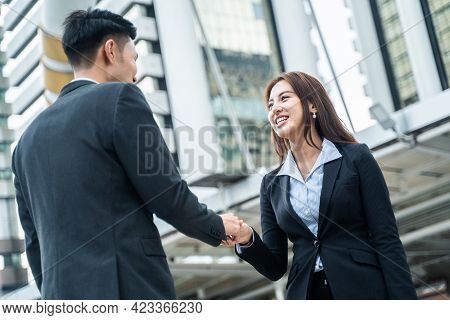 Asian Businesswoman And Man Make Handshake In The City Building In The Background. A Partnership Agr