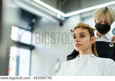 Asian Female Hairstylist Giving An Advise For Hairdo, Haircut And Color For Caucasian Woman Customer