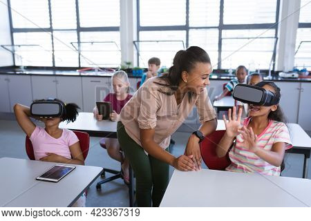 African american female teacher teaching a girl to use vr headset in the class at school. school and education concept