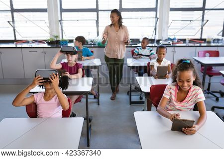 African american female teacher teaching students to use electronic devices in the class at school. school and education concept