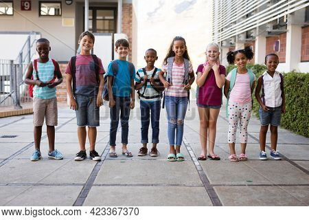 Portrait of group of diverse students smiling together while standing at school. school and education concept