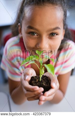 Portrait of african american girl holding a plant seedling in the class at school. school and education concept