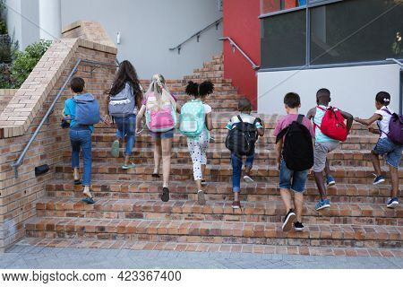 Rear view of group of diverse students with backpacks climbing up the stairs together at school. school and education concept