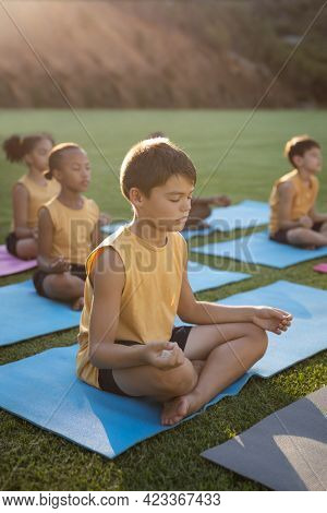 Caucasian boy practicing yoga and meditating sitting on yoga mat in the garden at school. school and education concept