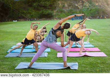 Female teacher and group of diverse students performing stretching exercise in the garden at school. school and education concept