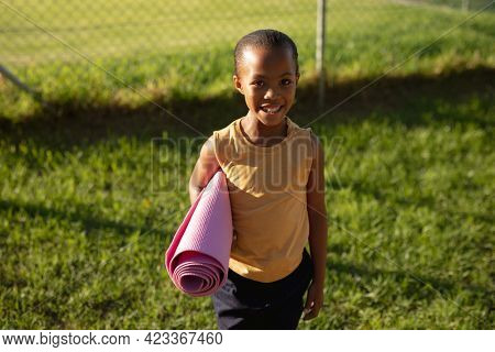 Portrait of african american girl smiling while while standing in the garden at school. school and education concept