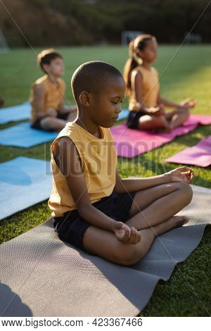 African american boy practicing yoga and meditating sitting on yoga mat in the garden at school. school and education concept