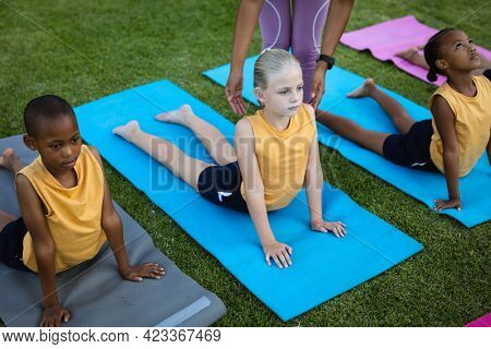 Mid section of female teacher correcting the form of caucasian girl in the garden at school. school and education concept