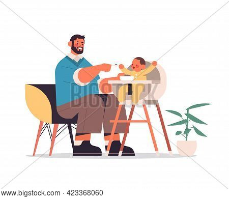 Young Father Feeding His Little Son On Kids Eating Chair Fatherhood Concept Dad Spending Time With H