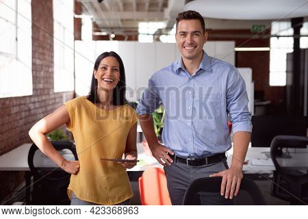 Portrait of happy caucasian male and female colleague standing at desk smiling, woman holding tablet. working in business at a modern office.