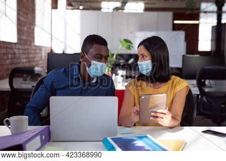 Diverse male and female colleague in face masks sitting at desk discussing, using laptop and tablet. working in business at a modern office during coronavirus covid 19 pandemic.
