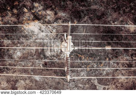 Drone Aerial Photograph Looking Down On A Telephone Pole And Wires In A Forest After Bushfire