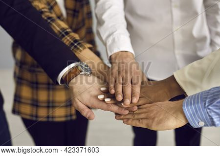 Team Of Diverse Business People Putting Hands Together In Corporate Work Meeting