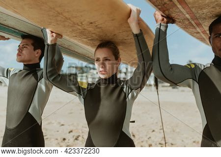 Surfers carrying the surfboard over their heads