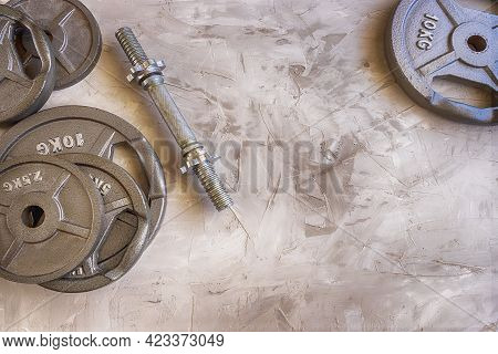 Weight Plates For Barbell Or Dumbbells In Cement Floor In Gym. Equipment  For Weight Training And  B