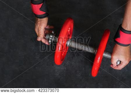 Man Hand Hold Red Dumbbells In Gym. Equipment  For Weight Training And  Exercises For Building Muscl