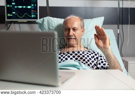 Cheerful Sick Senior Man Waving At Camera During Video Conference Using Laptop Laying In Bed, Breath