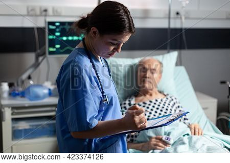 Medical Assistant Checking Treatment Of Senior Man Reading Notes On Clipboard. Sick Elderly Laying I