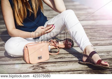 Girl Using White Mobile Phone. Young Girl Sitting On Wooden Floor Using Her White Mobile Device. Vin